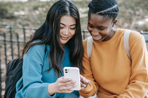 Cheerful multiethnic women browsing smartphone in park