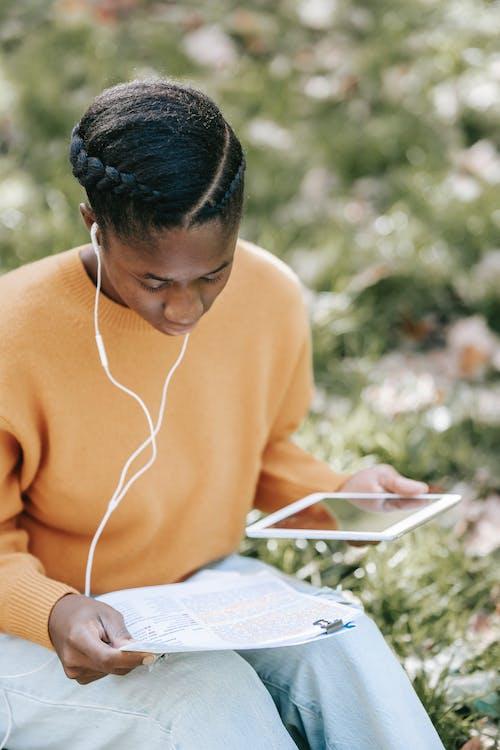 Человек в оранжевом свитере читает книгу