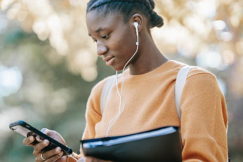 Low angle of young African American female student in casual clothes and earphones browsing mobile phone on street