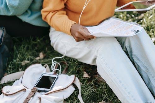 Человек в желтой рубашке с длинным рукавом и синих джинсовых джинсах сидит на белой ткани