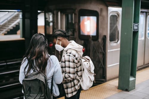 Faceless women in masks waiting for train