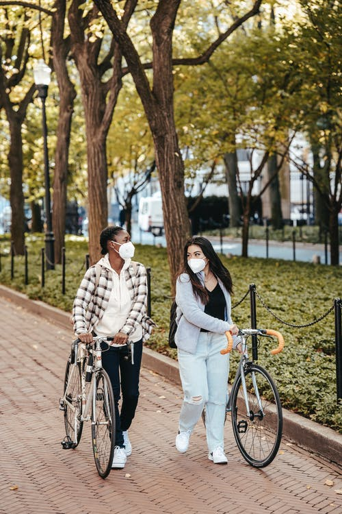 Cheerful women with bicycles in park