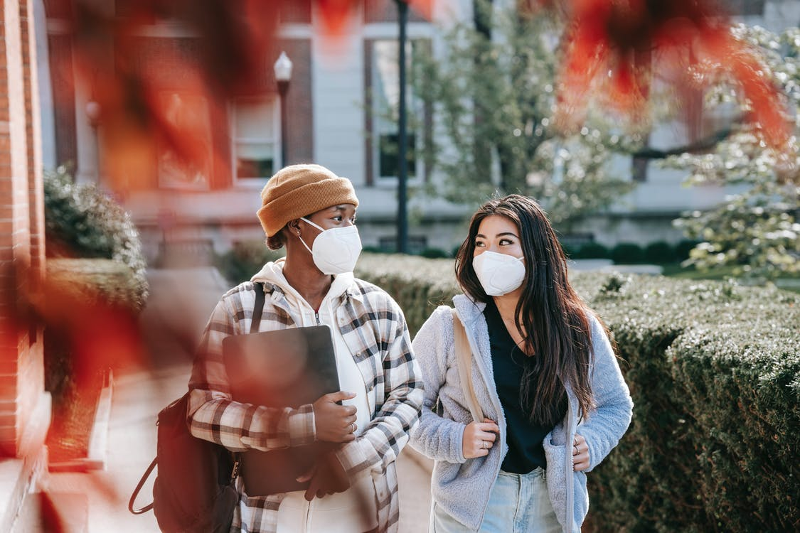 Young multiracial girlfriends in casual clothes with masks on faces strolling together in autumn park
