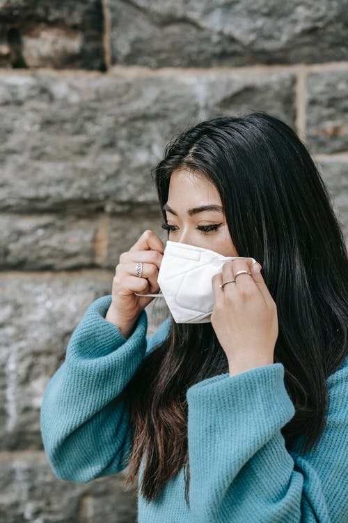 Young Asian female with dark long hair in warm sweater putting white protective mask on face