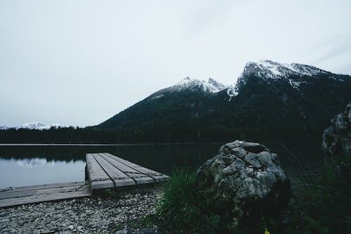 Peaceful mountainous lake with pier in highlands