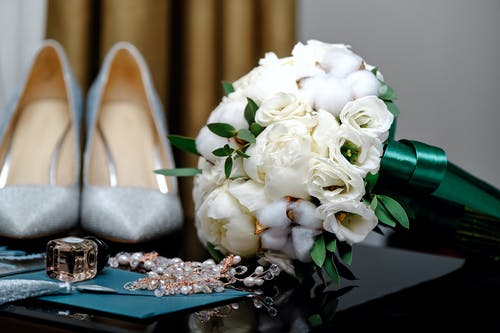 Bridal shoes and bouquet on table