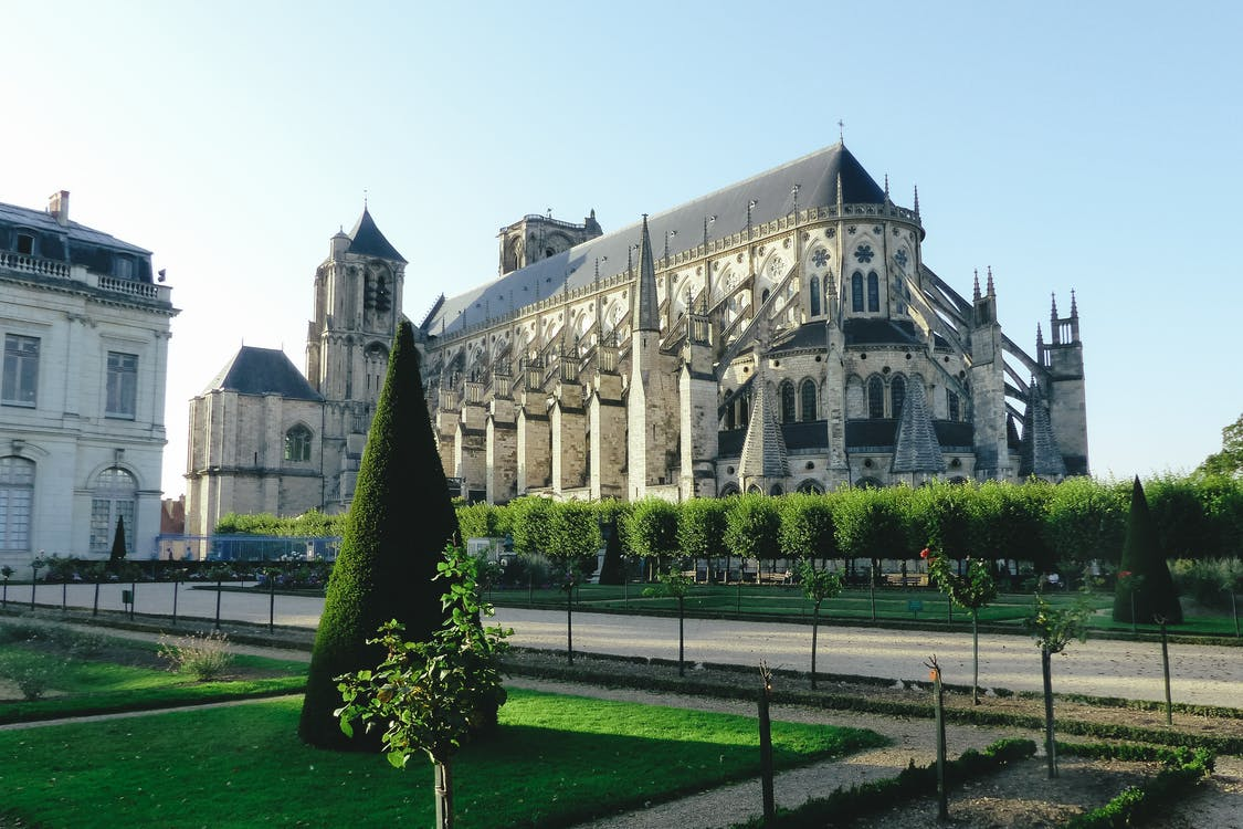 Exterior of aged monuments of national heritage of France Bourges Cathedral among green trimmed plants