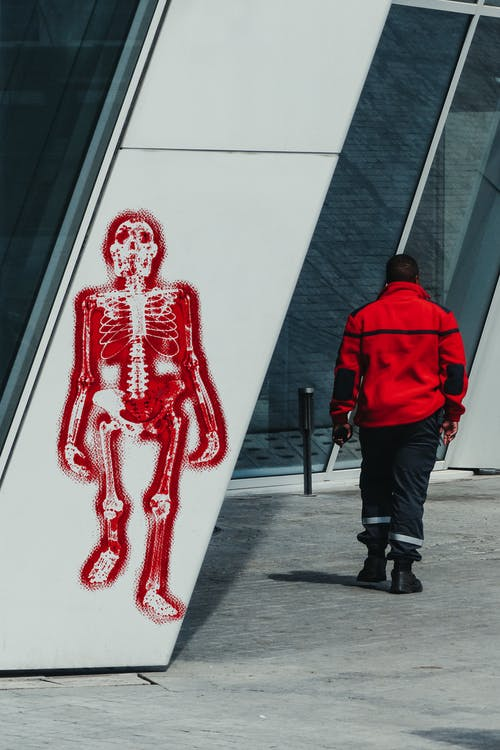 Back view of anonymous male wearing uniform walking past geometric building with artwork of skeleton
