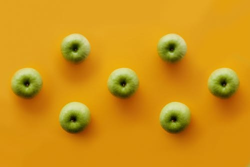 Green Round Fruits on Yellow Surface