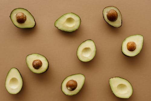 Avocado Fruits Cut In Half On Brown Surface