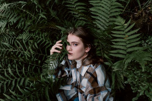 Woman in Plaid Button Up Shirt Standing Beside A Green Fern Plant