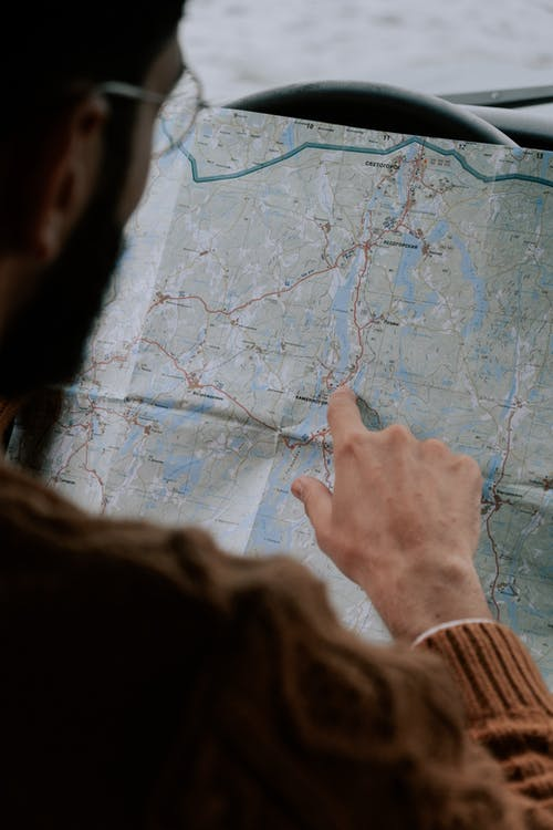 Person in Brown Long Sleeve Shirt Holding Map