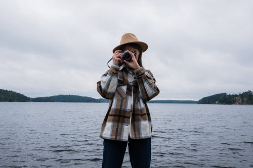 Person Wearing a Hat Taking a Picture