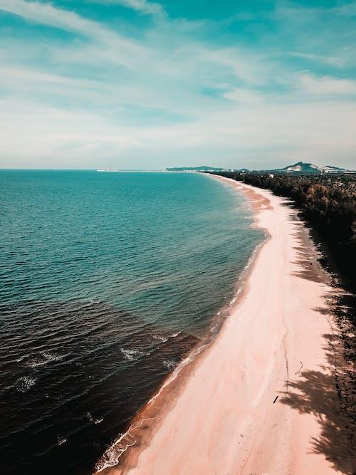 Tropical sandy seashore against blue sky in sunlight