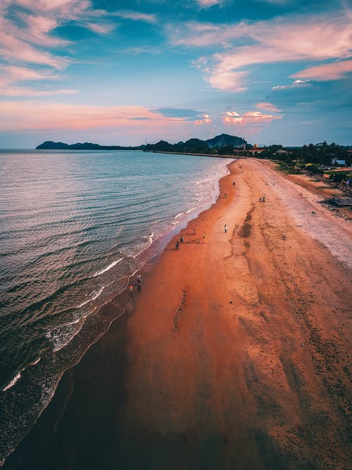 Breathtaking drone view of sandy beach of powerful waving ocean in tropical resort against cloudy sunset sky