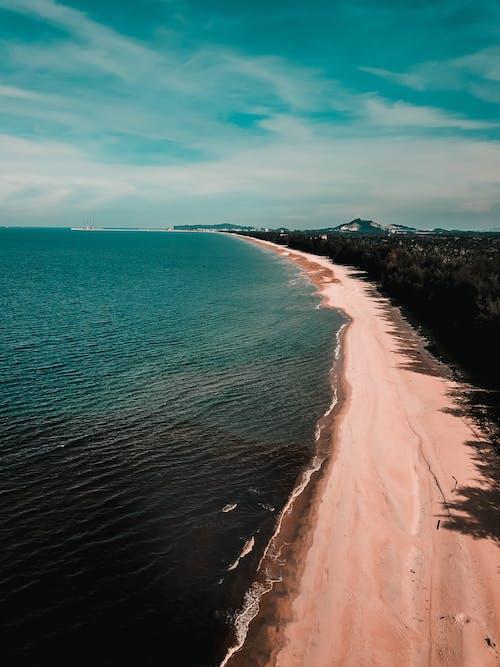 Sandy beach of waving ocean in tropical resort