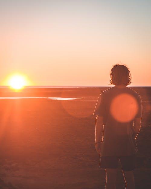 Unrecognizable man enjoying sunset on beach