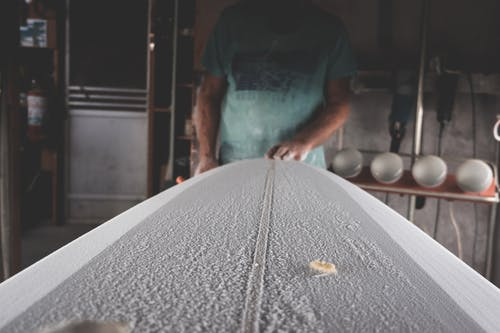 Crop artisan shaping surfboard in workshop