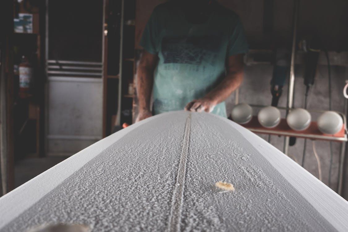 Crop artisan shaping surfboard in workshop