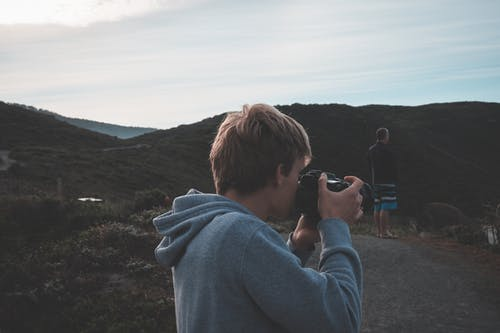 Side view of male photographer taking picture on professional photo camera while standing in mountainous area with man on background