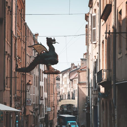 Sculpture of Graoully hanging in narrow avenue between residential buildings against cloudless sky on street of Metz in city of France