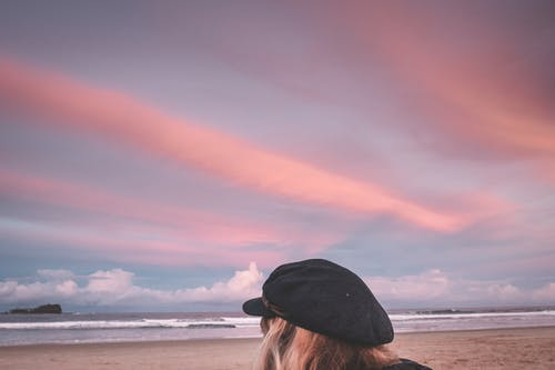 Unrecognizable woman on beach at sunset