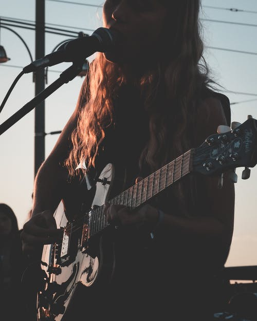 Crop unrecognizable female musician with wavy hair standing on stage and singing while playing electric guitar during concert