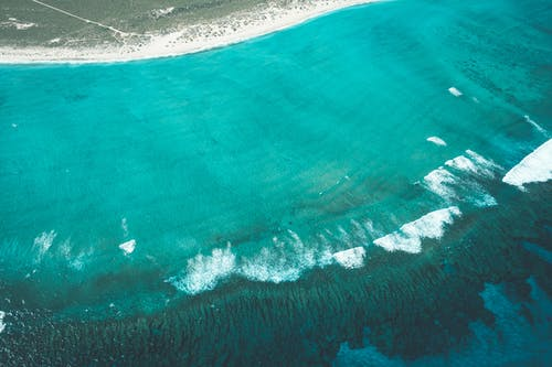 Drone view of turquoise water of ocean with foam and ripples near sandy shore