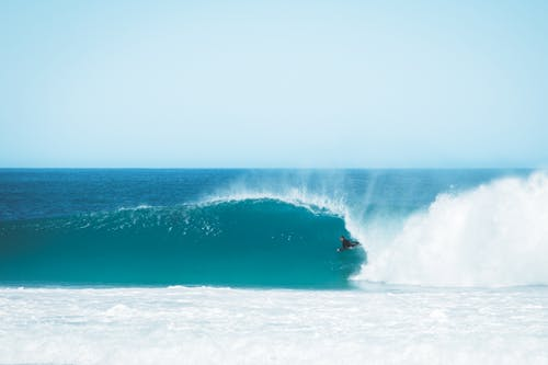 Distant surfer riding on foamy wave in azure ocean against cloudless sky while training in tropical resort on summer day