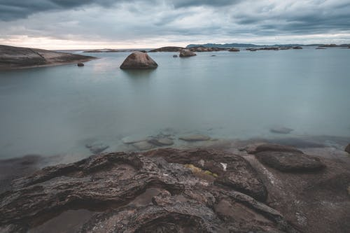 Amazing scenery of shallow rocky shore with tranquil seawater under majestic cloudy sky