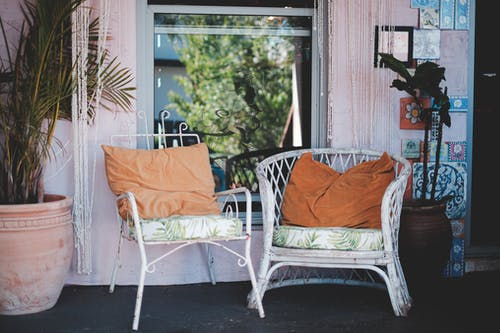 Comfortable wicker chairs with pillows placed on rural house terrace near window and potted houseplants on sunny day