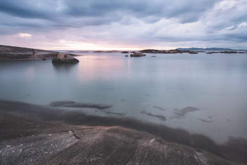 Magnificent scenery of tranquil rocky shore near tranquil seawater reflecting cloudy sky in overcast evening