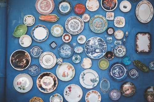 Composition of various decorative ornamental plates of different sizes and colors arranged on blue wall