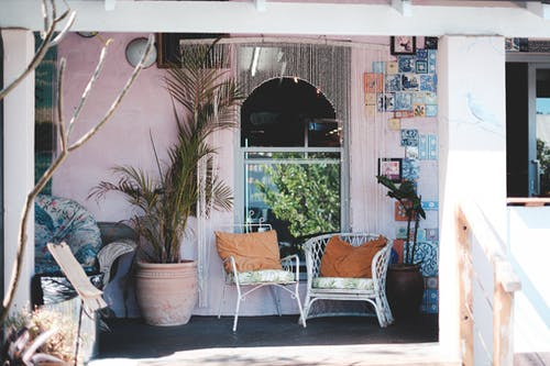 Sunny porch with comfy chairs and potted plants