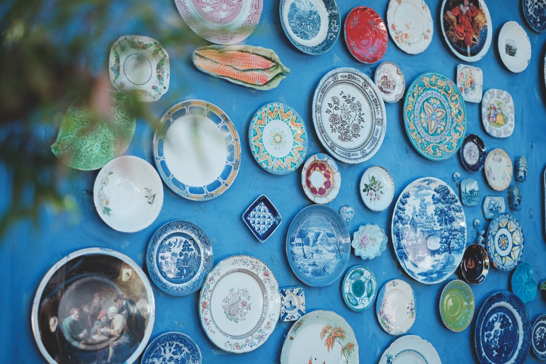 Collection of various ceramic plates of different sizes and ornaments arranged on bright blue wall in studio