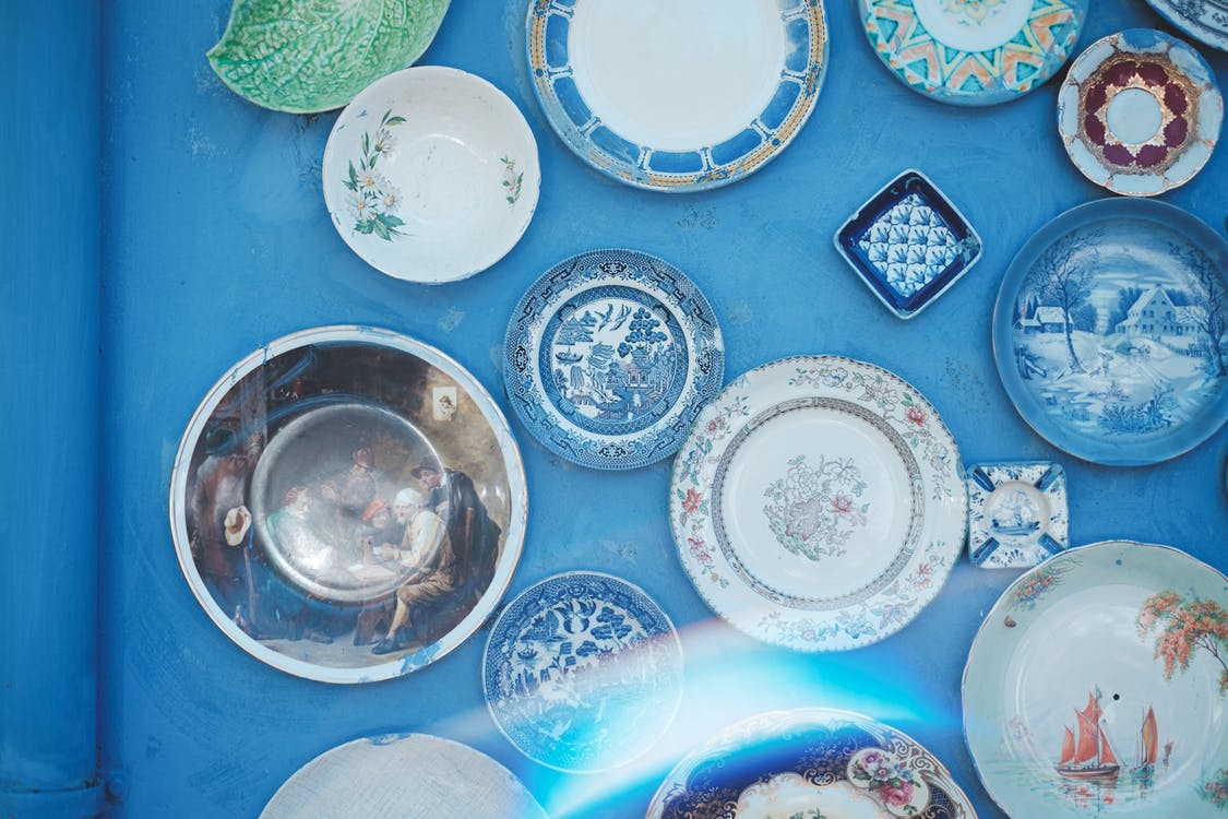 Assorted vintage plates of different sizes and ornaments hanging on bright blue wall in light studio