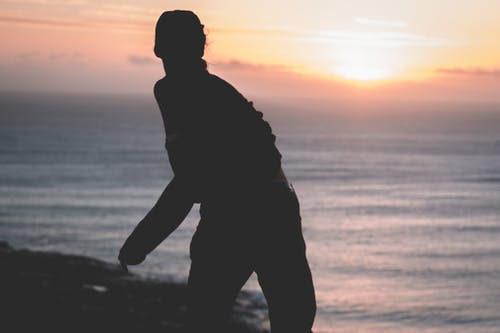 Unrecognizable person throwing stone in sea in evening