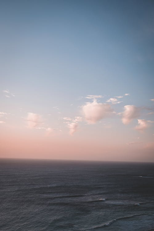 Scenic view of endless tranquil sea rippling beneath clear blue and pink sky in early evening