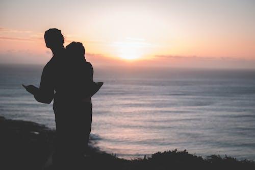 情侶站在海邊日落時的剪影