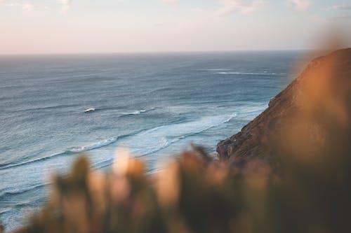 Wavy sea washing rocky steep coast
