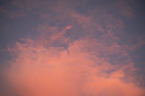 From below full frame of fluffy orange clouds floating over sundown sky at dusk