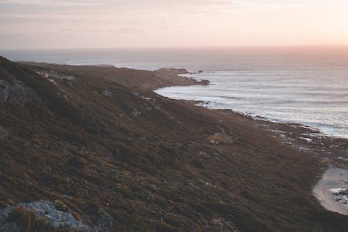 Rippling sea washing coast with mountain slope