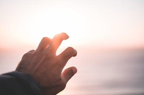 Crop anonymous male reaching hand to sun while standing near sea at sundown
