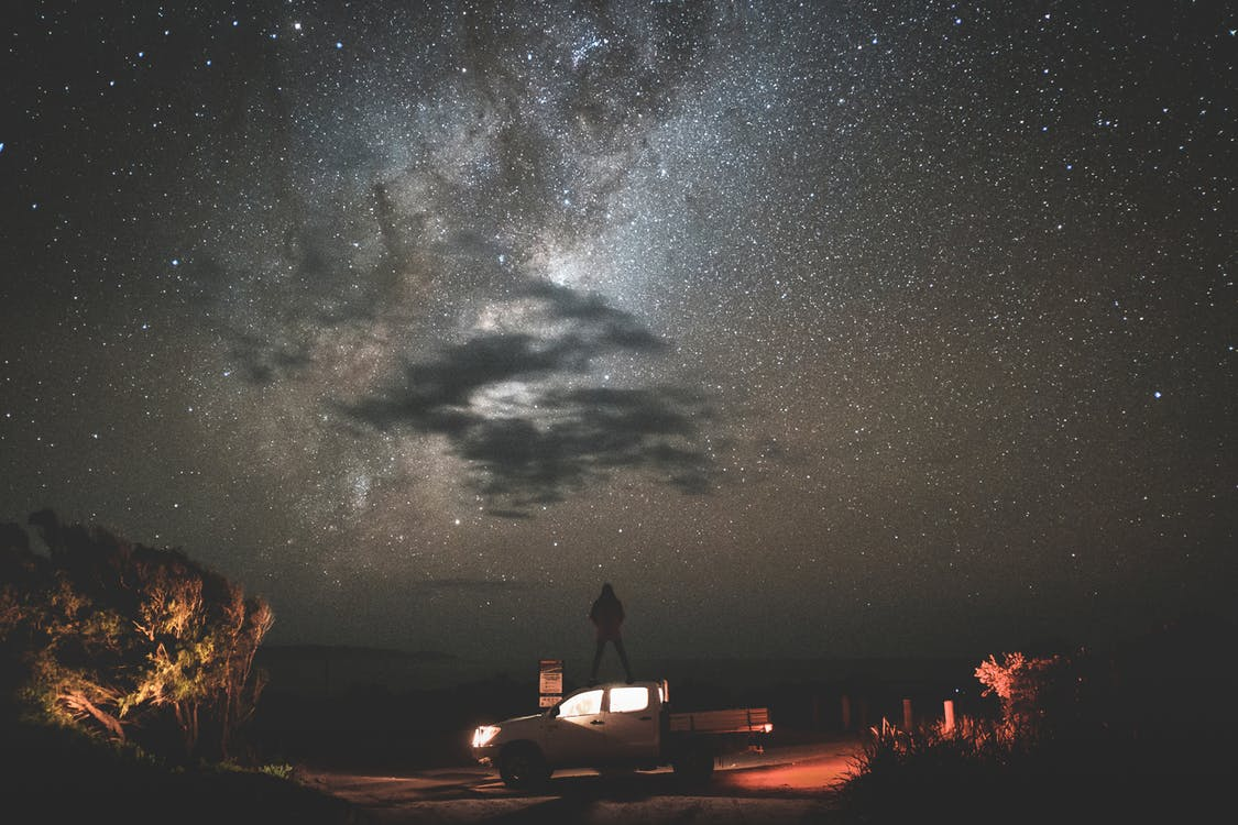 Traveler standing on car at starry night