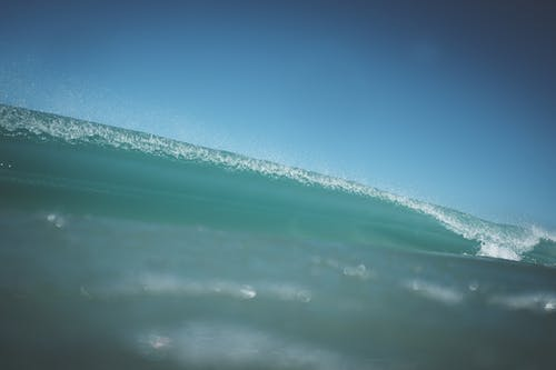 Powerful wave of turquoise ocean with transparent splatters rolling on crystal water in sunny day