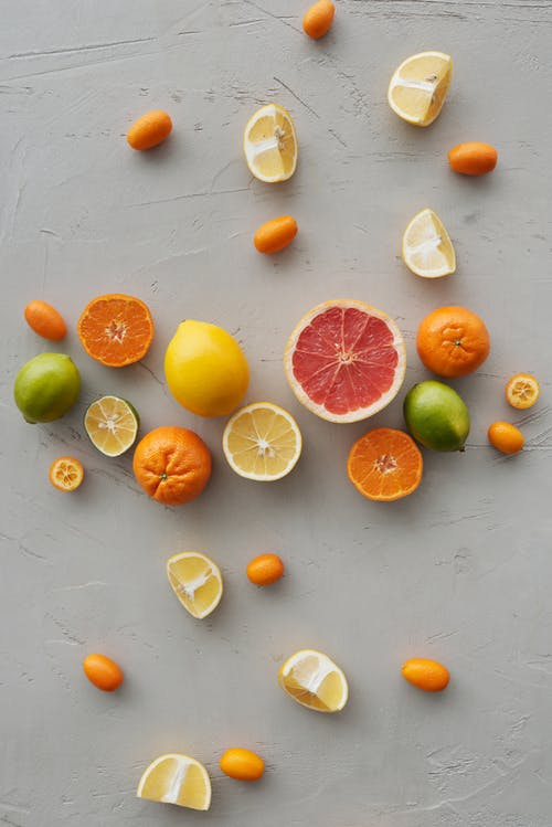 Photo Of Sliced Citrus Fruits On Gray Background