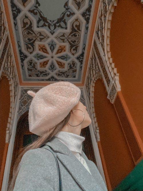 Woman in beret enjoying ornamental house
