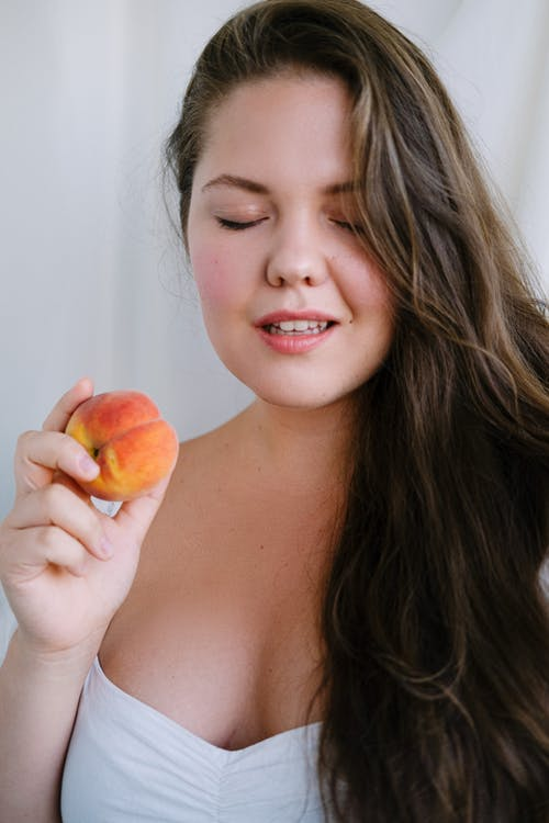 Content woman with ripe peach in hand