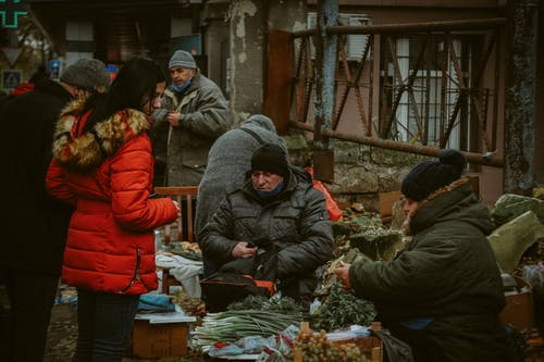 People in Black and Orange Jacket Standing in Front of Vegetable Display