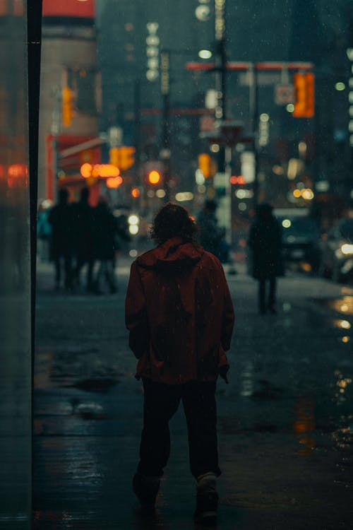 Person in Red Coat Standing on Sidewalk during Night Time